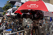 BBC brolley and camera in media village behind railings as tension mounts outside St Mary's Hospital, Paddington London, where media and royalists await news of Kate, Duchess of Cambridge's impending labour and birth. Some have been camping out for up to two weeks during a UK heatwave, having bagged the best locations where an heir to the British throne will eventually be shown to the world.