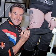NLD/Hilversum/20110211 - 3de Liveshow SBS Sterren Dansen op het IJs 2011, Gerard Joling zet een handtekeing onder een tatoeage van hem op het been van een fan