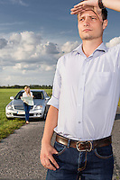 Young man shielding eyes with woman and car in background at countryside