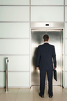 Businessman Waiting for Elevator rear view