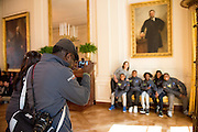 Students from Arthur Ashe Elementary in New Orleans wait under a portrait of Theodore Rooservelt before helping in the White House Kitchen Garden.