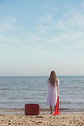 a girl in a white dress is standing on a beach with a red scarf and left a red suitcase behind her