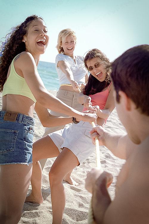 Playful couples tug-o-war on beach.