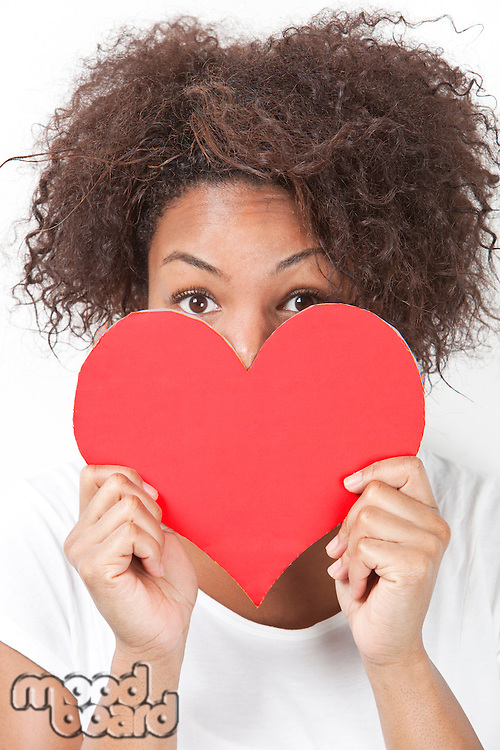 Portrait of African American young woman peeking over heart shape