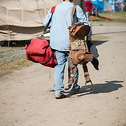 A cowboy goes home after a sun-bathed rodeo, with his gears and saddle.