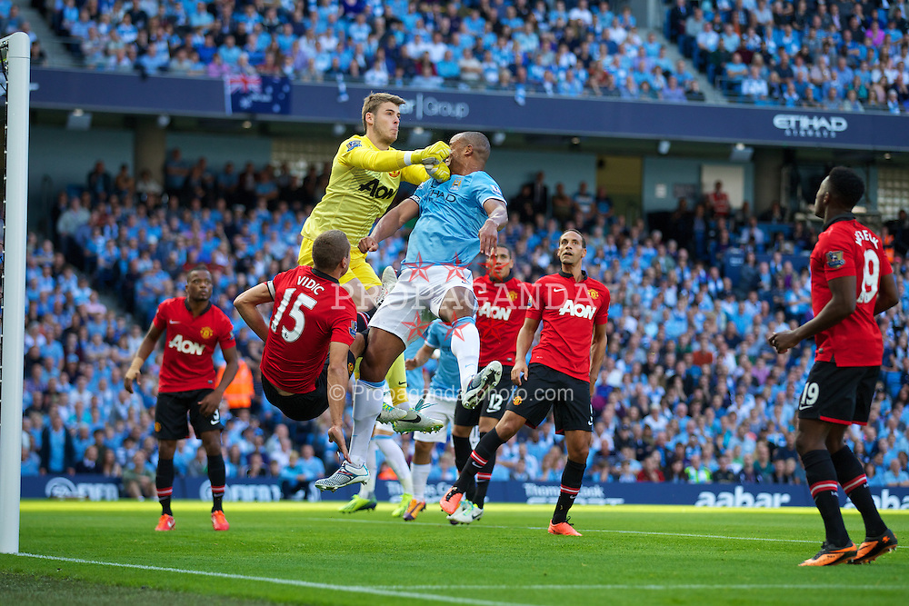 MANCHESTER, ENGLAND - Sunday, September 22, 2013: Manchester City's Vincent Kompany in action against Manchester United's goalkeeper David de Gea during the Premiership match at the City of Manchester Stadium. (Pic by David Rawcliffe/Propaganda)