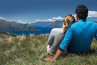 Couple cuddling looking over lake and hills back view