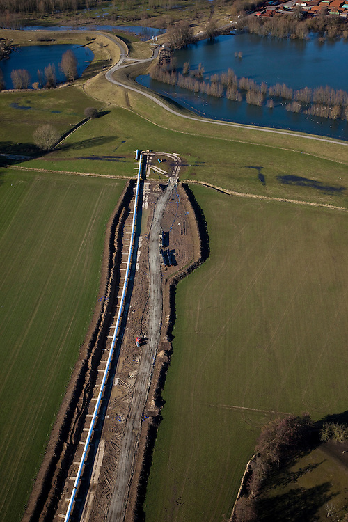 Nederland, Gelderland, Gemeente Beuningen, 07-03-2010; aanleg van een gastransportleiding even ten westen van Nijmegen ter hoogte van de rivierdijk van de Waal. De Waal zal worden gekruist door middel van een boring. De de pijpleiding maakt deel uit van de Noord-Zuid Route en wordt aangelegd in opdracht van de Gasunie in verband met toenemende vraag naar gas en een groeiende import en export van gas. .Construction of a gas pipeline just west of Nijmegen near the river Waal. The pipeline is part of the North-South Route and is commissioned by the Gasunie because of increasing gas demand and a growing import and export of gas..luchtfoto (toeslag), aerial photo (additional fee required).foto/photo Siebe Swart