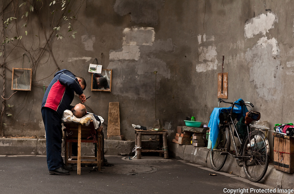 Getting a haircut in an alley in Chengdu