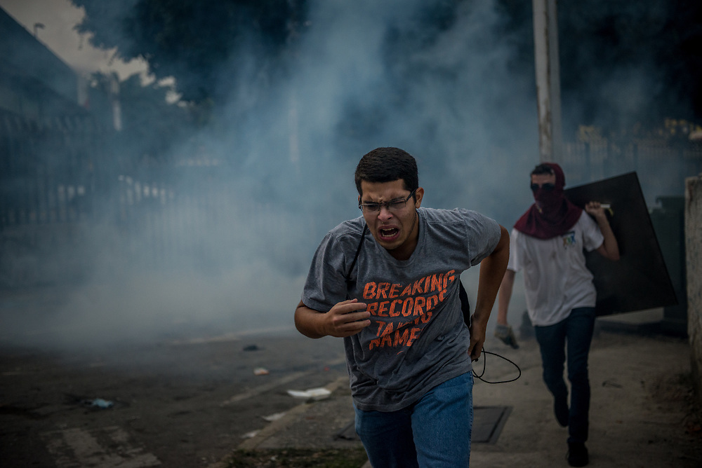 CARACAS, VENEZUELA - MAY 10, 2017:  Anti-government protesters run from being heavily tear gassed by the National Police. The streets of Caracas and other cities across Venezuela have been filled with tens of thousands of demonstrators for nearly 100 days of massive protests, held since April 1st. Protesters are enraged at the government for becoming an increasingly repressive, authoritarian regime that has delayed elections, used armed government loyalist to threaten dissidents, called for the Constitution to be re-written to favor them, jailed and tortured protesters and members of the political opposition, and whose corruption and failed economic policy has caused the current economic crisis that has led to widespread food and medicine shortages across the country.  Independent local media report nearly 100 people have been killed during protests and protest-related riots and looting.  The government currently only officially reports 75 deaths.  Over 2,000 people have been injured, and over 3,000 protesters have been detained by authorities.  PHOTO: Meridith Kohut