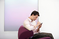 Casually dressed Businessman sitting on modern sofa Using PDA side view