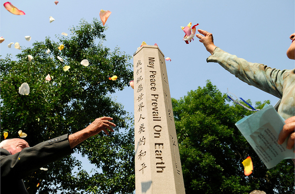 Members of the congregation throw rose petals on a peace pole during its dedication ceremony at Unity Church in South Bend, Ind., on July 27, 2008. The pole is in memory of longtime congregation member Robert Weed..
