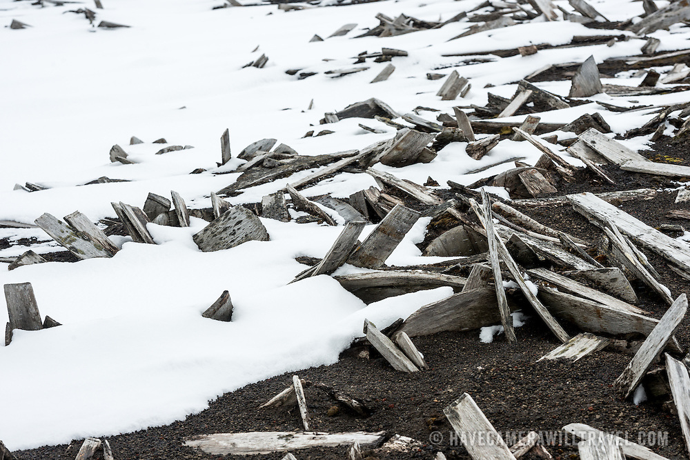 Shafts of wood lie on the beach partially covered in snow amongst the ruins of the former whaling station at Whalers Bay on Deception Island. Deception Island, in the South Shetland Islands, is a caldera of a volcano and is comprised of volcanic rock.