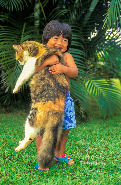 Happy 2 y.o. Hawaiian boy holding a large cat, Kauai, Hawaii