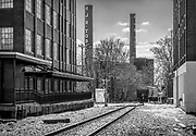 Looking south across Sixth Street as a pedistrian cross the railroad track just after a train passes by in downtown Winston-Salem