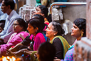 07 JANUARY 2014 - SINGAPORE:   Women pray during afternoon pooja in Sri Veeramakaliamman Temple, a Hindu temple located in Little India in the southern part of Singapore. The Sri Veeramakaliamman Temple is dedicated to the Hindu goddess Kali, fierce embodiment of Shakti and the god Shiva's wife, Parvati. Kali has always been popular in Bengal, the birthplace of the labourers who built this temple in 1881. Images of Kali within the temple show her wearing a garland of skulls and ripping out the insides of her victims, and Kali sharing more peaceful family moments with her sons Ganesha and Murugan. The building is constructed in the style of South Indian Tamil temples common in Tamil Nadu as opposed to the style of Northeastern Indian Kali temples in Bengal. PHOTO BY JACK KURTZ