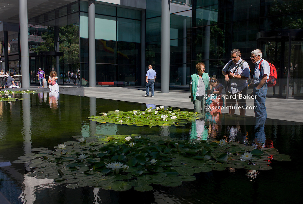 A family admire the water lillies floating on the surface of water in the pedestrian area of Spitalfields in central London.
