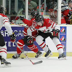 COBOURG, - Dec 16, 2015 -  Game #9 - Canada East vs Canada West at the 2015 World Junior A Challenge at the Cobourg Community Centre, ON. Maxime St. Pierre #25 of Team Canada East makes the hit on Tyson Jost #10 of Team Canada West<br /> (Photo: Amy Deroche / OJHL Images)