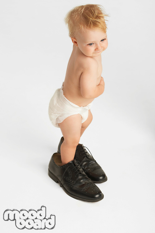 Baby Standing in Man's Shoes