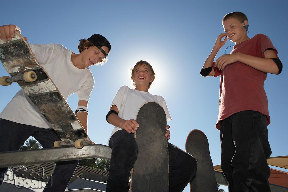 Three teenage boys (16-17) with skateboards outdoors