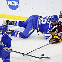 UMD's Nick Swaney (23) reaches for the puck while Air Force's Jonathan Kopacka (52) and Phil Boje (4) defend during the 2018 NCAA Hockey Championship - West Regional Final at the Denny Sanford Premier Center on Saturday, March 24, 2018 in Sioux Falls, S.D.