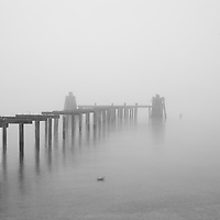 A delapidated and decayed old pier in the fog.