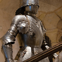 A knight in a suit of armor is posed atop an armored horse on display in the Alcazar in Segovia, Spain.