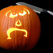 A carved jack-o-lantern with a look of surprise and dismay, with a knife stuck in it's head.