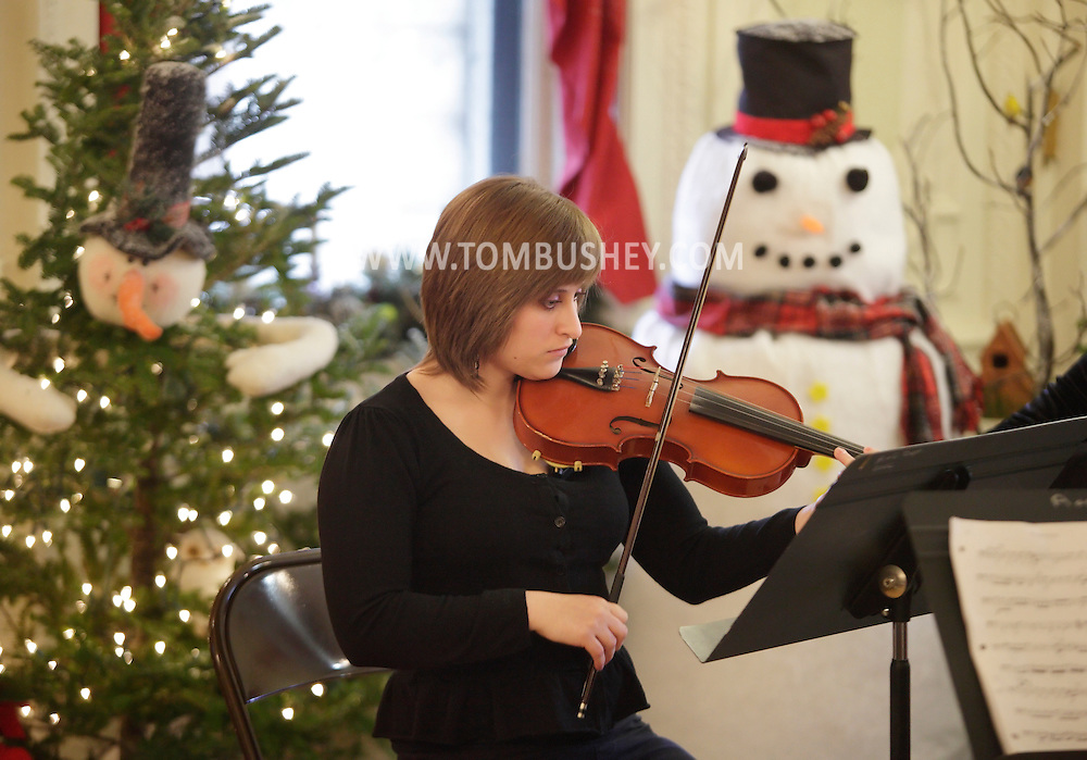 Middletown, New York - A member of the SUNY Orange Chamber Ensemble plays the violin during a concert at the Holiday Open House at the Morrison Hall mansion on Dec. 12, 2010. Morrison Hall was the home of the Morrison family, who donated the mansion to the college in 1950. The building is richly appointed with original Tiffany fixtures, lavish woodwork and C.W. Dodge ceiling murals.