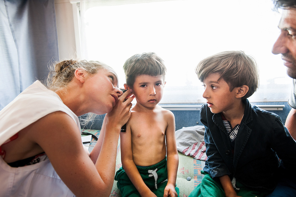 MSF doctor Anna Hoekstra examines two Afghan brothers at the mobile medical centre, a camper van of MSF at Mytiline port, Lesvos, Greece.