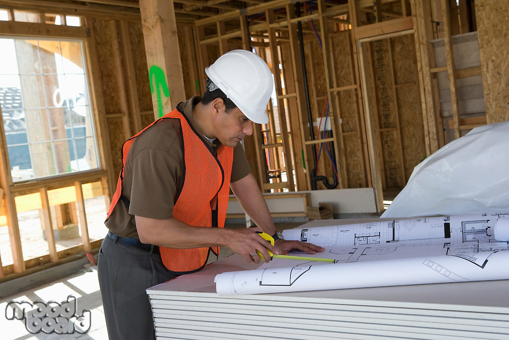 Construction worker using tape measure inside half constructed house