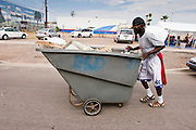 "07 AUGUST 2005 - PHOENIX, AZ: ALAN, who said he has lived on the streets of Phoenix for more than 10 years, pushes his dumpster past the Agape Harvest Church tents used for Sunday services. Alan said he collects garbage left on the street as a part of his ""atonement"" for past sins. The mile between the Phoenix police department headquarters and the Arizona State Capitol is also Phoenix's ""Skid Row"" where most of the homeless live and most of the homeless shelters and charity kitchens are located. Members of Agape Harvest Church come down to area on Sunday mornings and hold church services for the people in the area.  PHOTO BY JACK KURTZ"