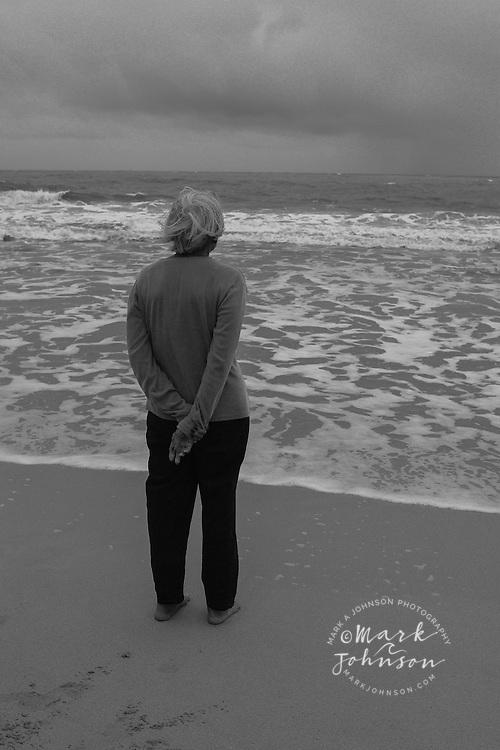 Senior woman on beach under stormy skies