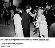 Hugh Grant &amp; Elizabeth Hurley being interviewed by T.V. crew at the  Oscar Night party hosted by Steve Tisch and Vanity Fair. Morton's. Los Angeles. March 1995. 95550/11<br />