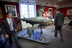 © Licensed to London News Pictures. 10/12/2012. London, UK. Two Bonham's employees walk past a large latex prop shark (est. £1000-1500) used in the 2010 'Doctor Who' Christmas Special 'A Christmas Carol' at an auction press view in Knightsbridge, London, today (10/12/12). The entertainment memorabilia auction, set to take place at Bonham's Knightsbridge auction house on the 12th of December, features props and costumes from film and TV as well as important Beatles pieces. Photo credit: Matt Cetti-Roberts/LNP