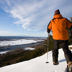 A man snowshoes above the Connecticut River Valley in Hadley, Massachusetts.  Mount Holyoke in Skinner State Park.  Metacomet-Monadnock Trail.