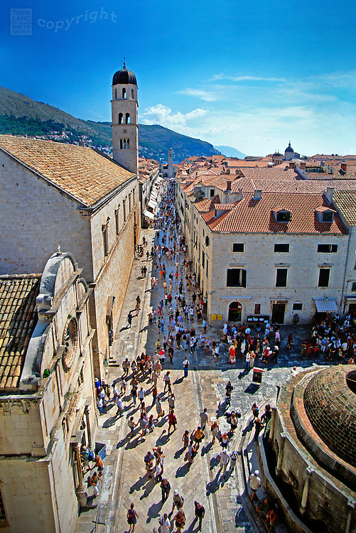 A view from atop the walls surrounding the old city of Dubrovnik, tourists as well as residents stroll past the Franciscan Church on The Stradun, Dubrovnik's main street. Since 1979, the historic center of Dubrovnik has been a UNESCO World Heritage Site.