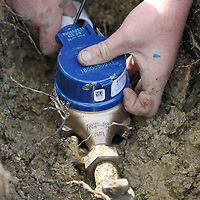 Trenton Abell finishes installation of a new digital water meter along Bobwhite Street in Tupelo.