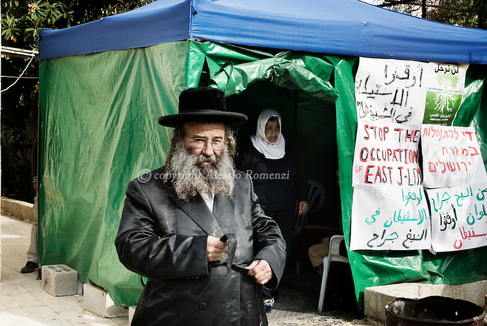 .A jewish settler walk past a palestinian kurd woman in the house's garden of the evicted Palestinian Kurd family in east Jerusalem's Sheikh Jarrah neighbourhood. Israeli settlers took over the house last month and hurled the Palestinian family's belongings into the street, armed with a court order secured after a protracted legal battle with the Palestinian family. In a confidential report dated on December 3, the European Union accused Israel of actively pursuing the annexation of Arab east Jerusalem and undermining hopes for peace with Palestinians. The annual report drafted by the EU heads of missions in Jerusalem accused Israel of implementing in 2009 an intricate policy which includes expanding Jewish settlements and demolishing Palestinian homes in east Jerusalem.© ALESSIO ROMENZI