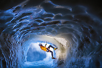A male climber ventures up icy walls of an exit ice tunnel at Aiguille du Midi, Chamonix, France on a sunny Summer afternoon.