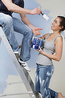 Man on ladder trying to paint woman