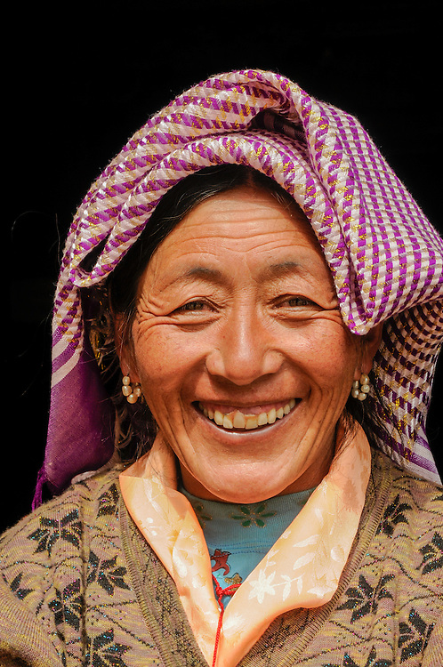 Tibetan woman laughing in front of the Drak Yangdzong monastery, Tibet.