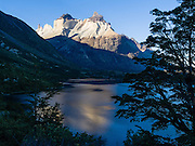 Los Cuernos (the Horns), Lake Skottsberg, Torres del Paine National Park, Chile, South America. The foot of South America is known as Patagonia, a name derived from coastal giants, or Patagoni, who were reported by Magellan's 1520s voyage circumnavigating the world and were actually Tehuelche native people who averaged 25 cm (or 10 inches) taller than the Spaniards.