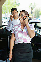 Business couple using mobile phones near car