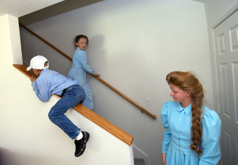Rebekah (cq)  foregroudn, and Danielle background, both daughters of FLDS mother Sarah Barlow Draper watches as Abram (cq) slides down the banister in their home in Abilene, Texas on Monday June 2, 2008. They had reunited with their mother following the court order which released the children back into the custody of their mothers. August MIller/ Deseret News .