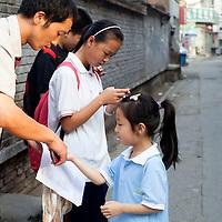 BEIJING, JULY12-14,2013 : Die juengste Teilnehmerin des Foto Workshops  wird von ihrem Vater belehrt, bevor sie sich aufmacht, in ihrer Schule zu fotografieren.