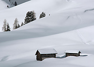 Two old wooden barns surrounded by deep snow in the Dolomites, South Tyrol, Italy