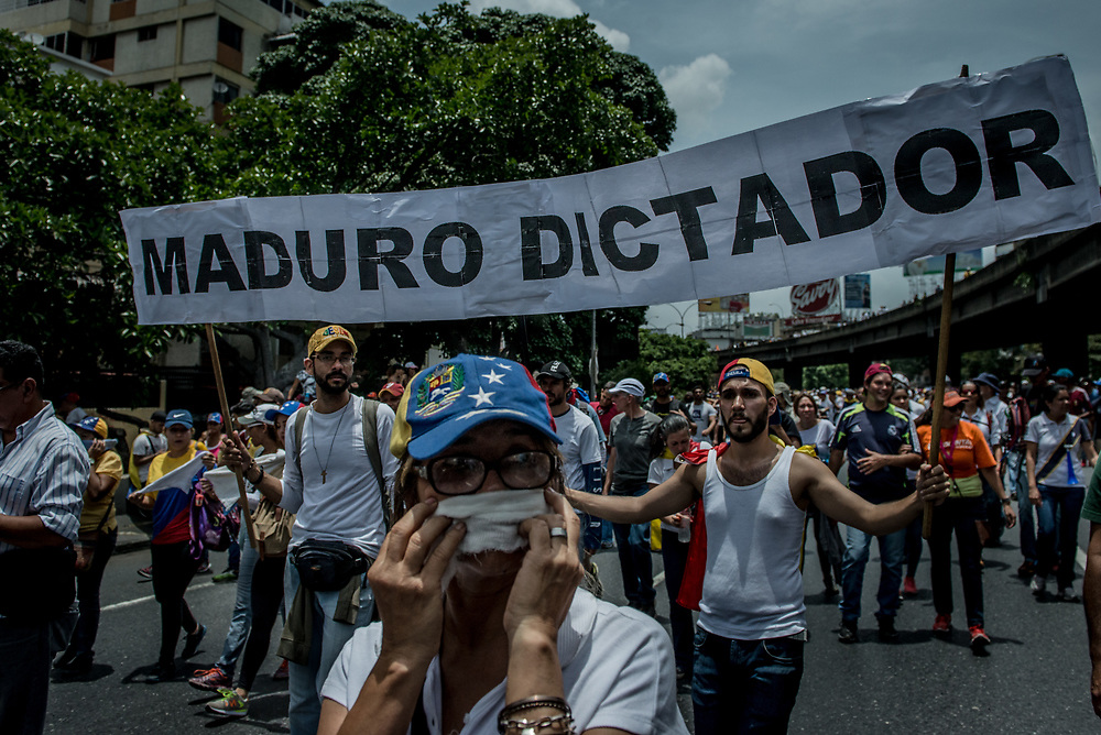"CARACAS, VENEZUELA - APRIL 19, 2017:  Protesters hold a sign that says ""Dictator Maduro"". Thousands of protesters took to the streets today in Venezuela to show their discontent with the government.  They were met by riot police that fired tear gas and rubber bullets at them.  Some protesters responded by throwing rocks and petrol bombs.  Venezuela is in crisis, and residents face daily struggles over food and medicine shortages, and one of the highest crime rates in the world.  PHOTO: Meridith Kohut"