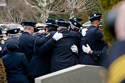 Philadelphia, PA, USA - December 13, 2014; On Ivy Hill Cemetery in Philadelphia firefighters attending the funeral of firefighter Lt. Joyce Craig-Lewis embrace each other as the ceremony comes to an end. (photo by Bas Slabbers)<br /> <br /> <br /> Scene from Ivy Hill Cemetery in Philadelphia during the funeral of Lt. Firefighter Joyce Craig-Lewis who died in the line of duty fighting a blaze in the West Oak Lane Section of the city.<br /> <br /> Posthumously promoted to Lieutenant, Firefighter Joyce Craig-Lewis of the Philadelphia Fire Dept. was laid to rest at Ivy Hill cemetery on December 13, 2014. Lt. Craig-Lewis of Engine Company 64 is the first female firefighter of the Philadelphia Fire Dept. who has died in the line of duty. The fire department of Philadelphia is the oldest in the nation.