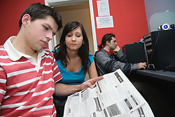 Czech couple looking in job section of newspaper for work,